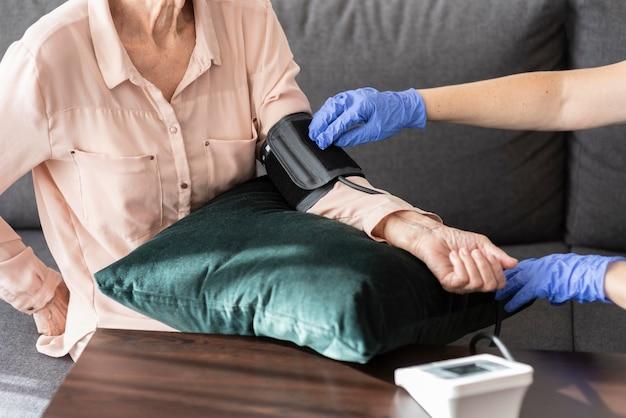 Donna anziana che si fa controllare la pressione sanguigna dall'infermiera