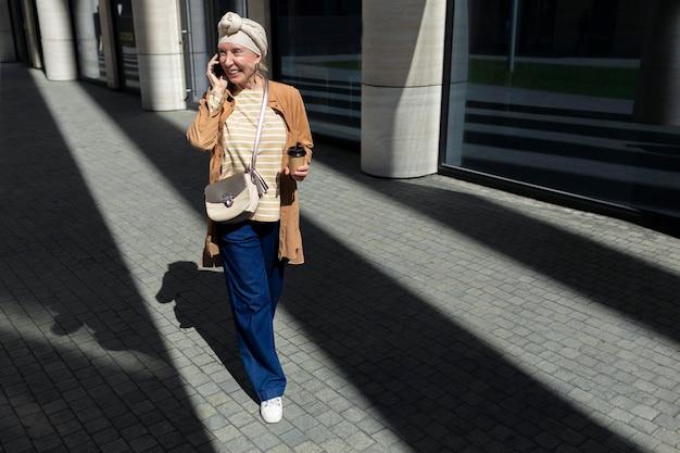 Donna anziana all'aperto in città parlando al telefono mentre beve caffè