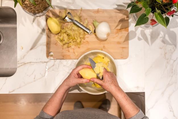 Mani della donna anziana che tagliano una patata per preparare una frittata spagnola con la cipolla
