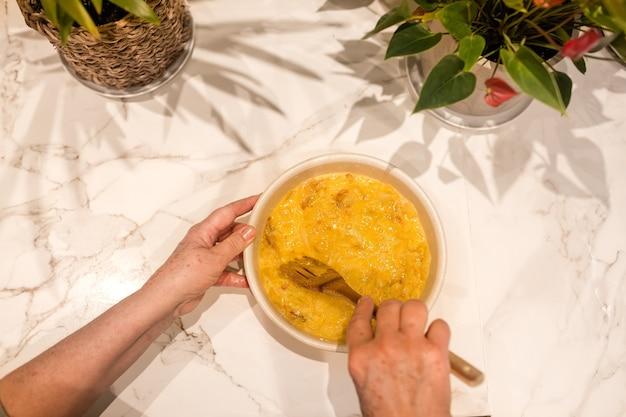 Le mani della donna anziana mescolando uova e patate con cipolle per cucinare una frittata di patate