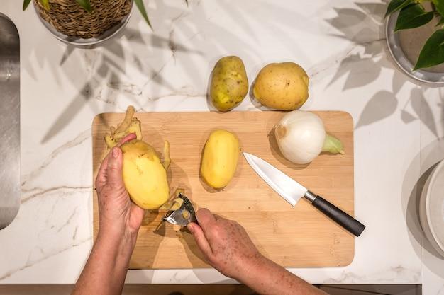 Mani della donna anziana che sbucciano una patata su legno per fare una frittata di patate con cipolla