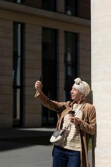 Donna anziana che prende selfie con lo smartphone all'aperto in città