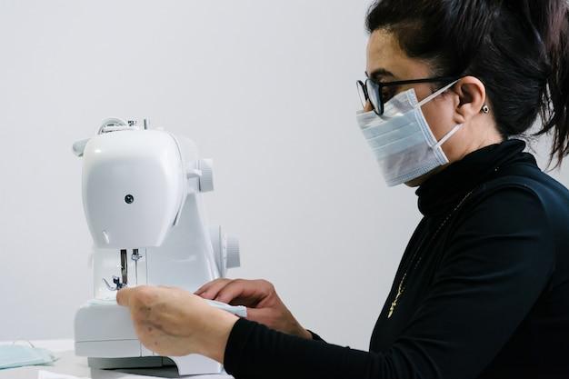 Una donna anziana si offre volontaria per cucire maschere per combattere il virus. cucendo su una macchina da cucire bianca. aiutare la comunità. pandemia di coronavirus.