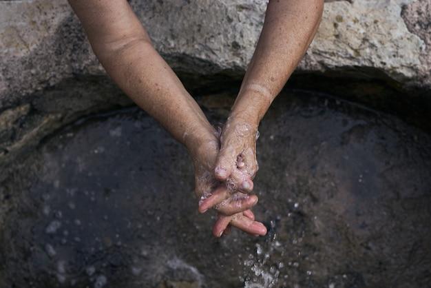 La donna anziana si lava le mani