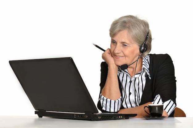 Donna anziana con un computer portatile su sfondo bianco
