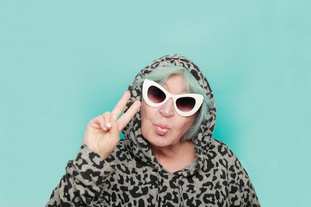 Donna anziana con occhiali da sole e smorfia baciante su sfondo blu - nonna moderna plus size con occhiali da sole alla moda