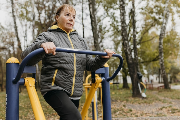 Donna anziana che lavora fuori all'aperto con lo spazio della copia