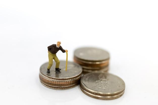 Oldman in piedi sulla pila di monete