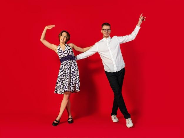 Oldschool stile giovane coppia danzante isolato su sfondo rosso