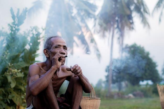 Ole uomo sta fumando sul campo.