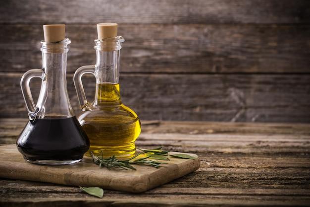 Olio d'oliva e aceto balsamico su un fondo di legno