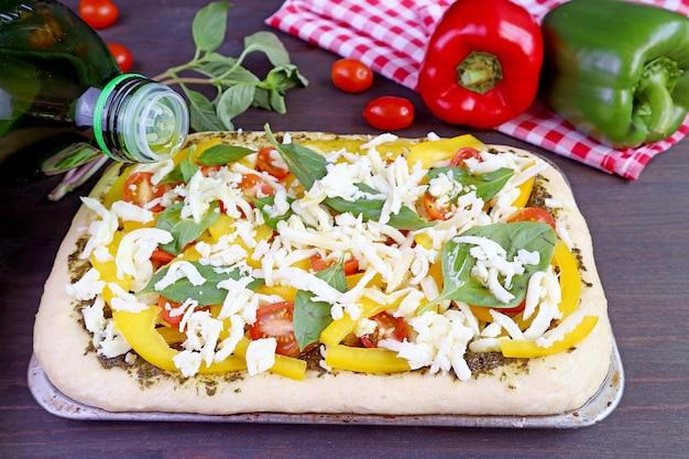 L'olio d'oliva viene fatto cadere sull'impasto della pizza riempito con condimenti salutari colorati