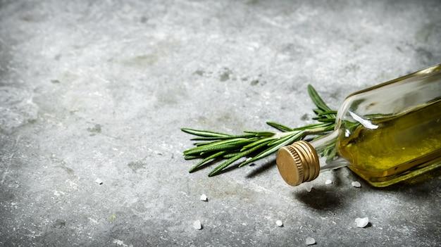 Olio d'oliva in bottiglia al rosmarino e sale su fondo di pietra