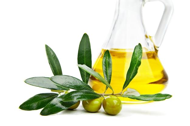 Olio d'oliva e ramo con olive su bianco