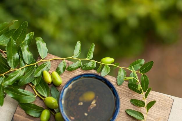 L'olio d'oliva nella tazza. ramo di un ulivo con olive fresche. olive verdi. in giardino. su una tavola di legno. una brocca per l'olio. classici italiani. olive d'italia. food of italy