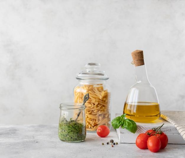 Olio d'oliva in una bottiglia di vetro, pasta in un barattolo e salsa al pesto di basilico. cucina sana