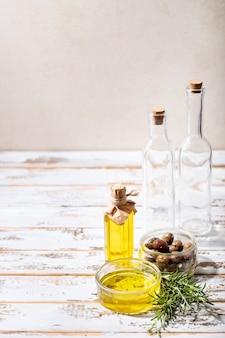 Olio d'oliva in una ciotola di vetro servito con olive fresche su sfondo bianco in legno