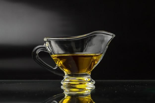 Olio d'oliva in una salsiera di vetro su una superficie nera