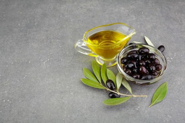 Olio d'oliva in vetro con olive nere e foglie copyspace su fondo rustico