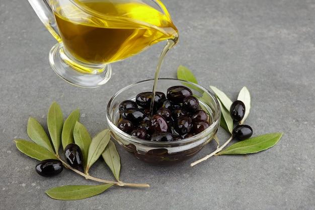 Olio d'oliva in vetro con olive nere e foglie su fondo rustico