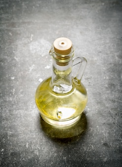 Olio d'oliva in una brocca. su sfondo di pietra.