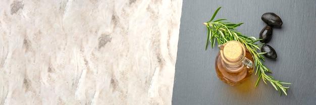 Olio d'oliva. olive su uno sfondo di olio d'oliva. una bottiglia versa l'olio in un primo piano del piattino. piano del tavolo in pietra nera con posto per testo o design. banner o immagine panoramica.