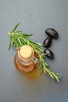 Olio d'oliva. olive su uno sfondo di olio d'oliva. una bottiglia versa l'olio in un primo piano del piattino. piano del tavolo in pietra nera con posto per testo o design.