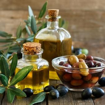 Olio d'oliva e olive su tavola in legno rustico