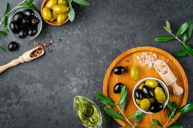 Olio d'oliva e olive con foglie e sale rosa su superficie scura. vista dall'alto, copia dello spazio