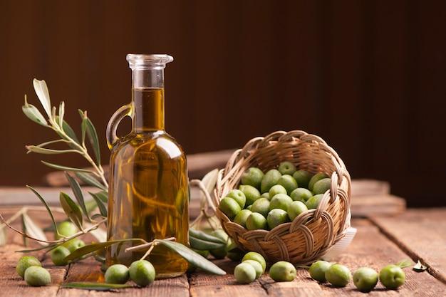 Olio d'oliva e olive su tavola rustica in legno