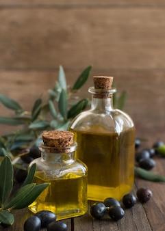 Olio d'oliva e olive sulla tavola di legno