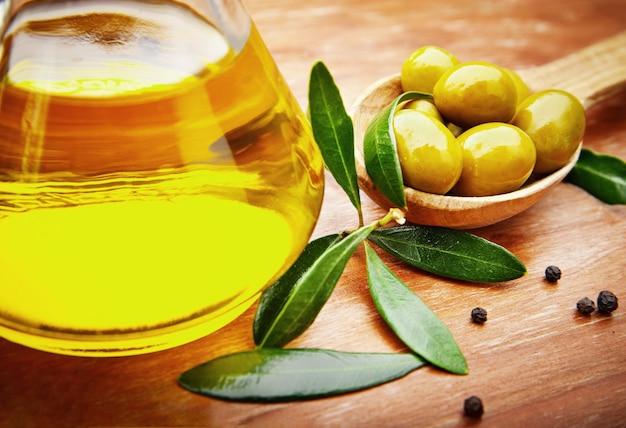 Olio d'oliva con olive fresche su legno rustico