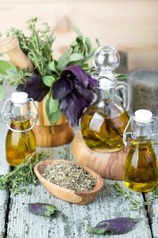 Olio d'oliva con erbe e spezie su fondo in legno