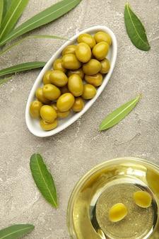 Olio d'oliva con oliva su sfondo grigio. foto verticale