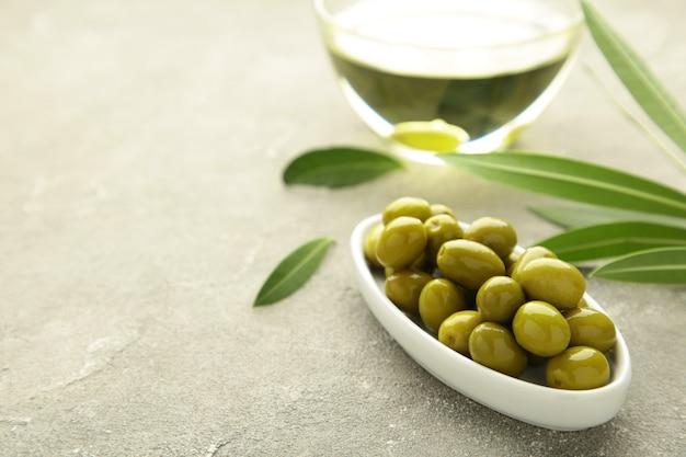 Olio d'oliva con oliva su sfondo grigio con copia spazio.