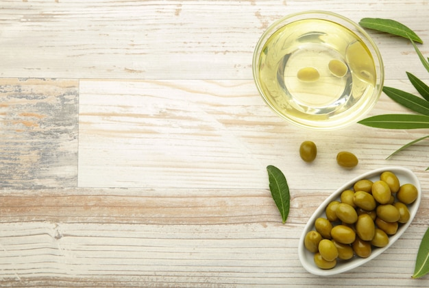 Olio d'oliva con oliva su sfondo bianco. vista dall'alto