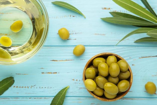 Olio d'oliva con oliva con foglie su sfondo blu. vista dall'alto