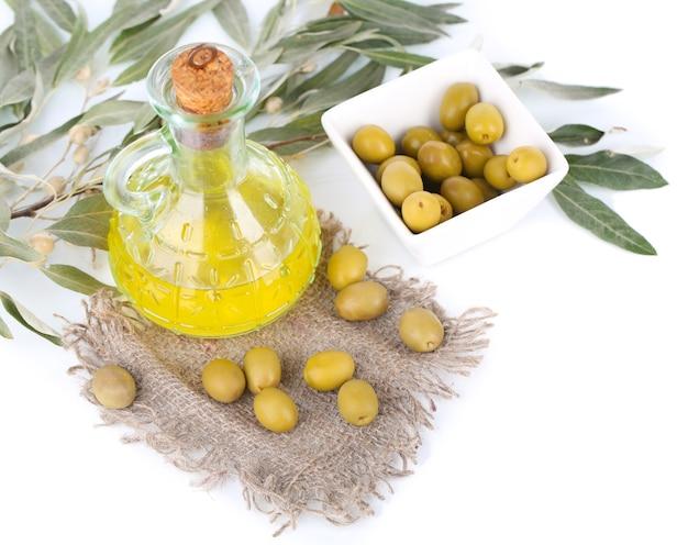 Olio d'oliva con olive in una ciotola e ramo su tela di sacco isolato su bianco