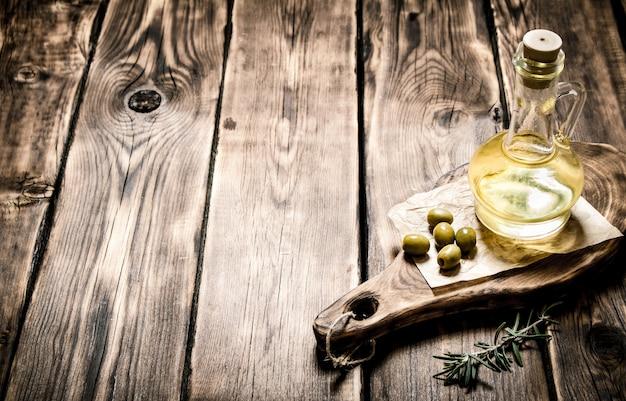 Olio d'oliva con rametto di rosmarino. sullo sfondo di legno.