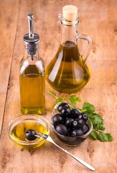 Olive e bottiglie sane di olio d'oliva e tazza con prezzemolo