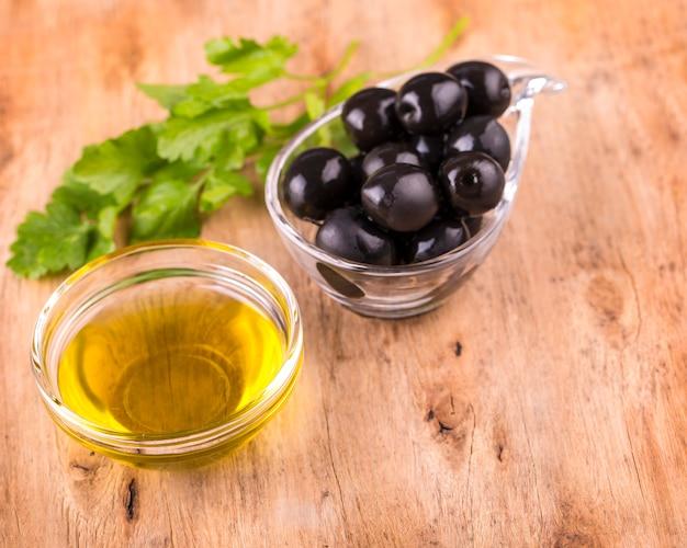 Olive e tazza sana dell'olio d'oliva con prezzemolo sulla vecchia tavola di legno