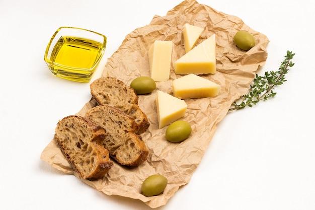 Olive, parmigiano e rametti di timo su carta. vista dall'alto.