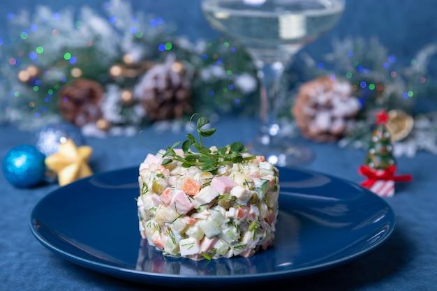 Insalata olivier su un piatto blu, decorata con germogli di piselli. tradizionale insalata russa di natale e capodanno