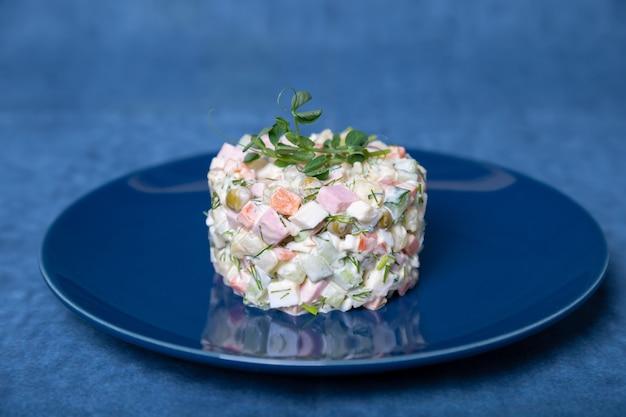 Insalata olivier su un piatto blu, decorata con germogli di piselli.