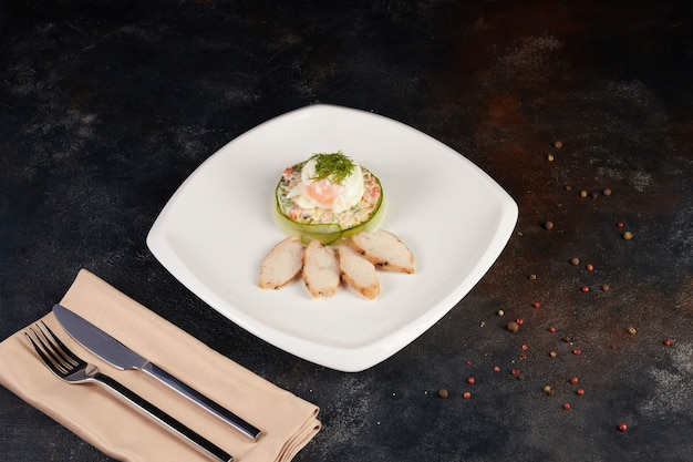 Insalata olivier servita su foglie di spinaci su un piatto quadrato bianco
