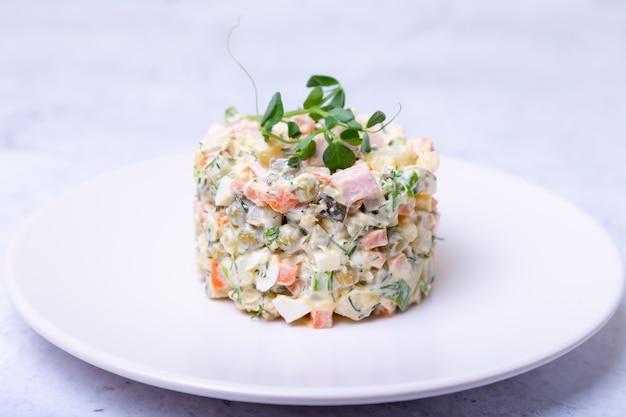 Insalata olivier su un piatto bianco, decorata con germogli di piselli. insalata russa.