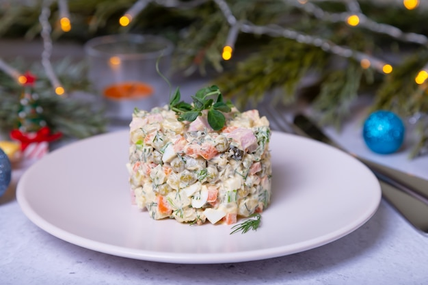 Insalata olivier su un piatto bianco, decorata con germogli di piselli Foto Premium