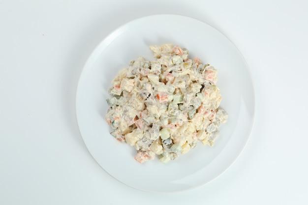 Insalata di olivier sul piatto bianco. versione vegana della tradizionale insalata russa olivier di verdure bollite.