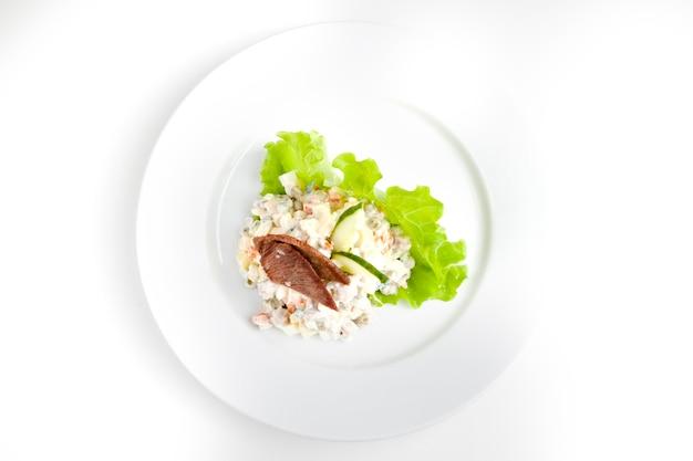Insalata olivier con erbe su un piatto bianco e un piatto bianco