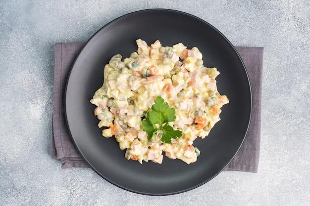 Insalata olivier con maionese su un piatto. il russo è un piatto festivo tradizionale. Foto Premium